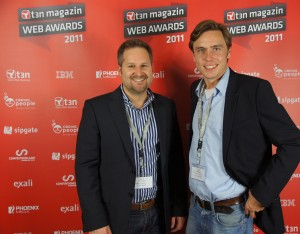"""exali-Account Manager Philipp Locher (rechts) und ich posieren stolz wie Oskar auf dem """"roten Teppich"""" – und vor der Foto-Wand auf der auch unser Sponsoren-Logo von exali zu sehen ist."""